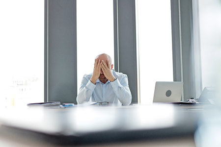 mid adult: Tired mid adult businessman covering face at desk in office LANG_EVOIMAGES