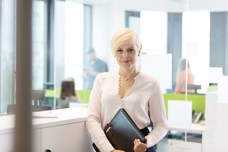 incidental people: Portrait of confident mature businesswoman with file in office