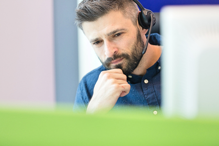 mid adult: Thoughtful mid adult businessman wearing headset at office
