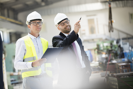 mid adult: Mid adult male supervisors having discussion in metal industry