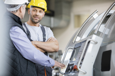 mid adult: Mid adult manual worker having discussion with colleague by machinery in industry LANG_EVOIMAGES