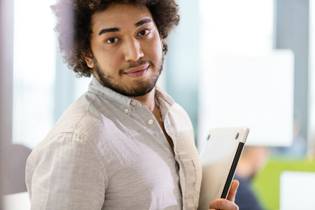 incidental people: Portrait of confident young businessman holding laptop at office LANG_EVOIMAGES