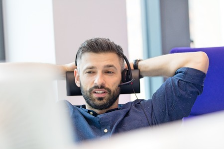 mid adult: Mid adult businessman using headset in office