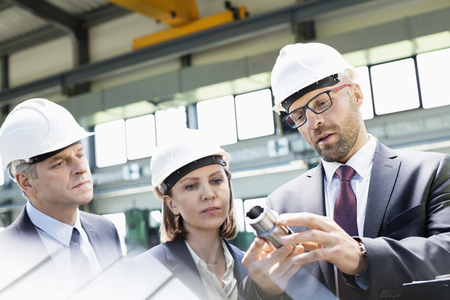 machine part: Mid adult businessman explaining machine part of colleagues in metal industry