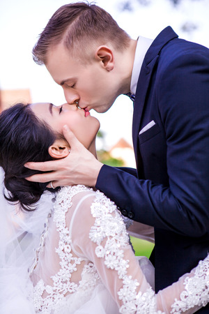 Side view of romantic wedding couple kissing against sky