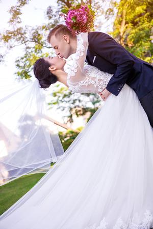 boca cerrada: Vista lateral de los pares de la boda que se besan en el césped LANG_EVOIMAGES