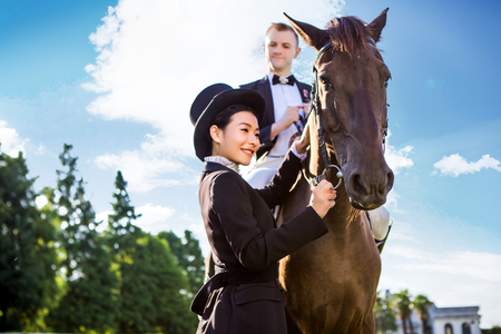 quarter horse: Side view of happy woman standing by man sitting on horse against sky LANG_EVOIMAGES