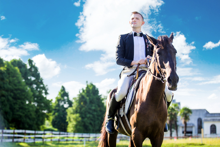 uomo a cavallo: Thoughtful well-dressed man sitting on horse against cloudy sky LANG_EVOIMAGES