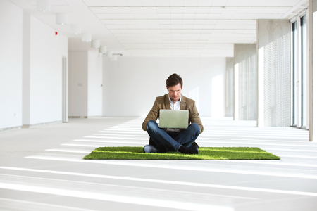 Full length of young businessman using laptop while sitting on turf in new office