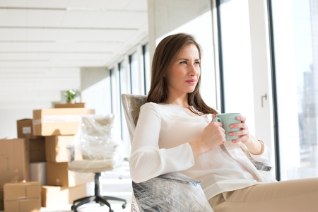 Thoughtful young businesswoman holding coffee cup in new office