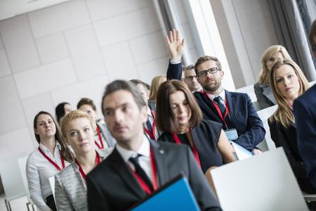 selective focus: Businessman raising hand during seminar at convention center