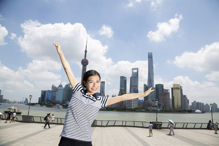 Portrait of happy woman standing with arms outstretched on promenade against Pudong skyline Stock Photo