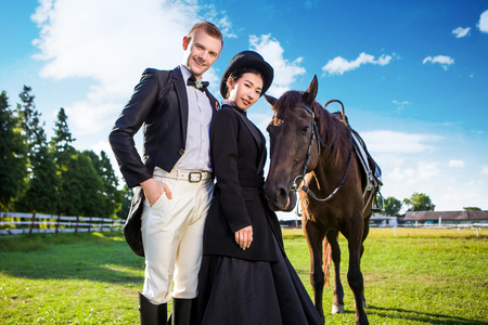 black hat: Portrait of confident well-dressed couple standing with horse on field