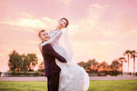 Side view portrait of happy bridegroom carrying bride on field during sunset 版權商用圖片