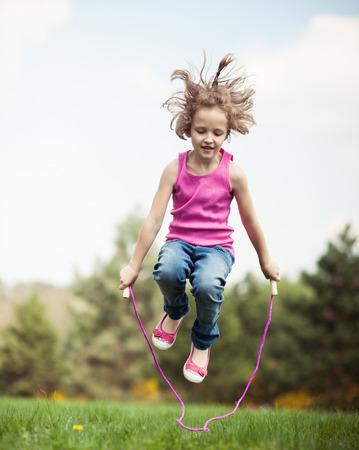 Young girl skipping in park Reklamní fotografie