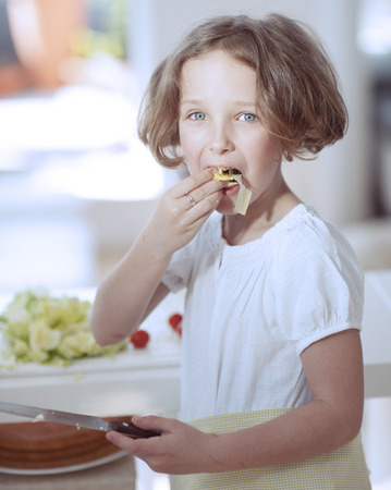 Young girl eating salad whilst holding knife in kitchen Stock Photo