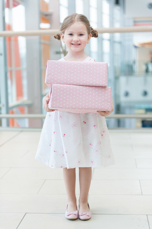 laden: Young girl holding two gift wrapped boxes
