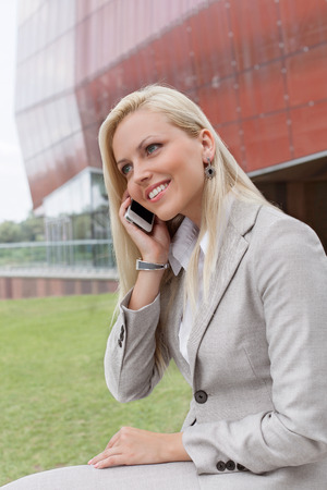 Young businesswoman conversing on mobile phone against office building