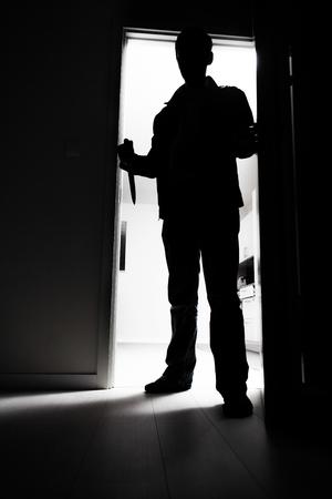 Longitud total de ladrón con cuchillo entrando en cuarto oscuro