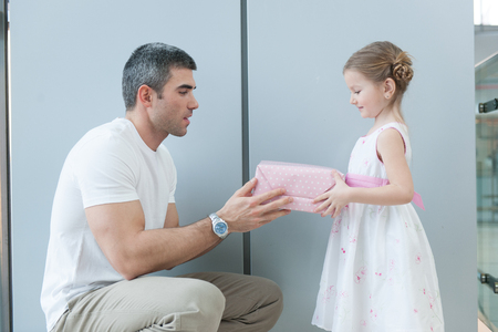 laden: Young girl handing present to her father