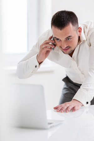 Businessman using mobile phone and looking at computer Stock Photo