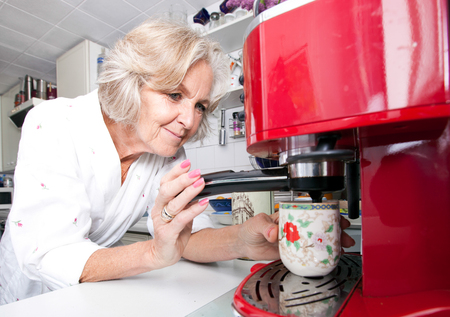 Senior woman dispensing coffee from machine at kitchen counter LANG_EVOIMAGES