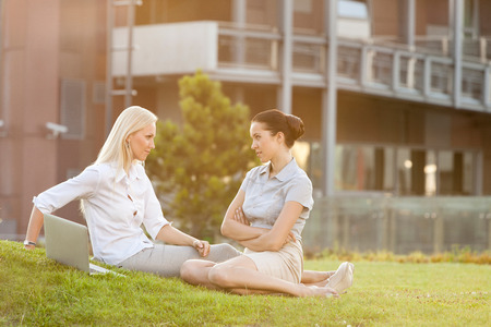 Young confident businesswomen looking at each other in office lawn