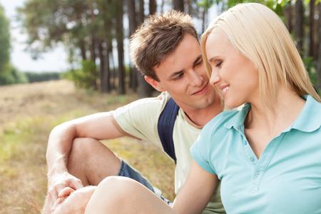 Romantic male hiker looking at woman while relaxing in forest