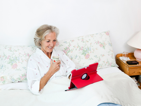 Happy senior woman using digital tablet while having coffee on bed at home Stock Photo