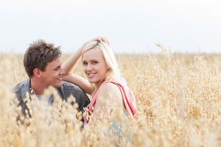 mujer mirando el horizonte: Portrait of beautiful young woman sitting with boyfriend amidst field