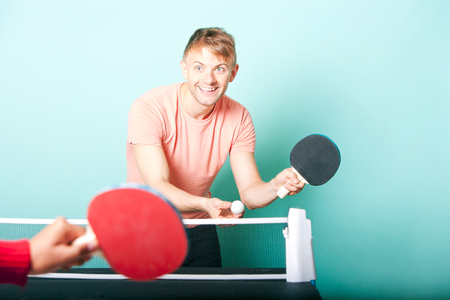 Caucasian man playing table tennis with friend LANG_EVOIMAGES