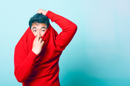 Young Asian Man trying to take of Red Sweater LANG_EVOIMAGES