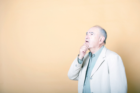 looking away from camera: Senior adult man with his hand on his chin looking up inquisitively LANG_EVOIMAGES