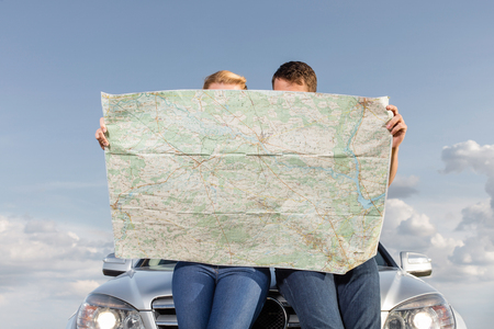 Couple reading map while leaning on car hood during road trip Stock Photo