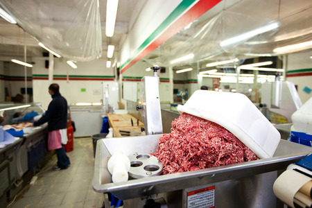 commercialism: Minced meat in container with employee standing in background at store LANG_EVOIMAGES