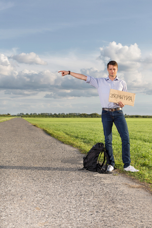 Full length portrait of young man with anywhere sign gesturing on countryside