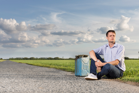 vanishing point: Full length of young man with empty gas can sitting by country road LANG_EVOIMAGES