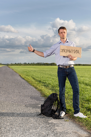anywhere: Full length of young man hitching while holding anywhere sign on countryside