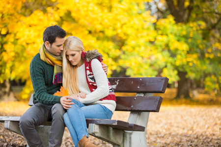 Passionate young man hugging shy woman on park bench during autumn LANG_EVOIMAGES