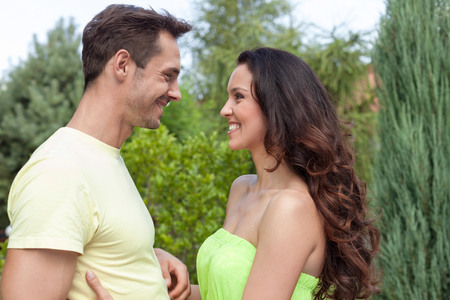 Side view of smiling young couple looking at each other in park Stock Photo