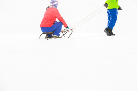 Low section of young man pulling woman on sled Stock Photo