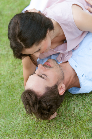 cabeza abajo: High angle view of romantic young couple lying together in park