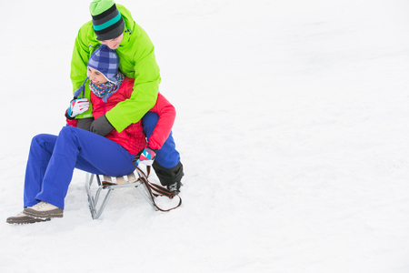 Young man embracing woman on sled in snow Stock Photo