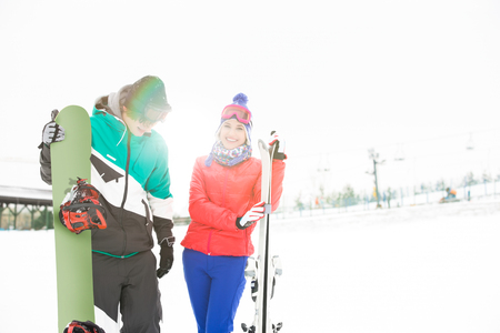 Happy young couple with snowboard and skis in snow Stock Photo