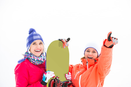 Smiling female friends with snowboard outdoors