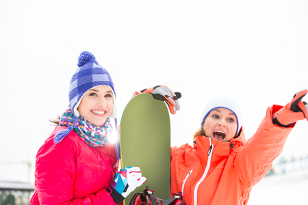 Excited female friends with snowboard outdoors