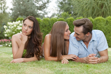 Loving young couple ignoring female friend in park LANG_EVOIMAGES