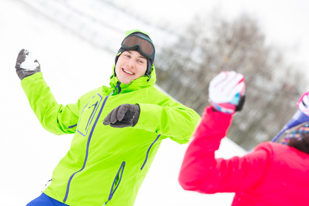 Happy young man throwing snowball towards woman Stock Photo