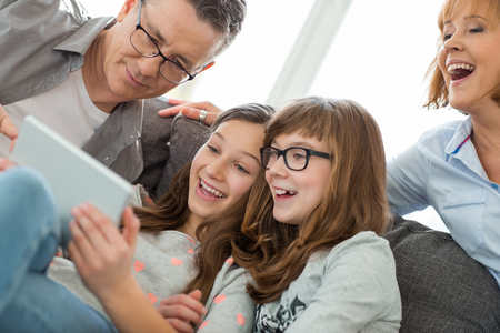 Cheerful family using tablet PC at home LANG_EVOIMAGES