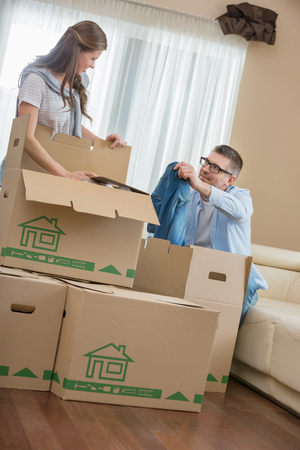 couple on couch: Couple unpacking cardboard boxes in new house